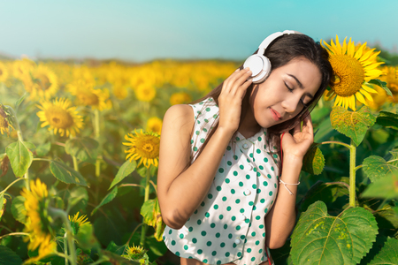 Beautiful girl listening music in field of sunflower in the morning.