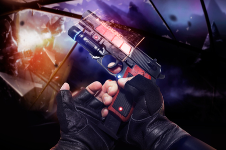 Photo for Hand in black gloves holding a red neon recharging handgun. First person view hand in black leather gloves holding a futuristic fantasy neon recharging handgun with clip and neon red, blue indicators. - Royalty Free Image
