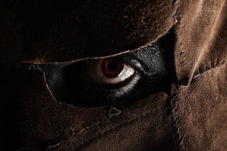 Photo pour Clouseup photo of a evil monster murderer eye face part in sewed leather mask on black background. - image libre de droit