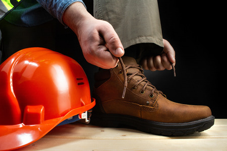 Photo pour Photo of a worker lacing up leather boot on a surface with protective helmet. - image libre de droit