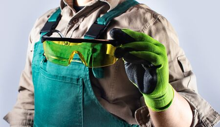 Photo of a worker in green overall outfit with protective gloves holding glasses torso view.