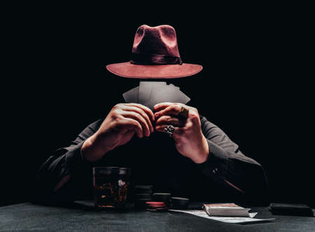 Photo for Photo of a shaded gangster in black shirt and hat playing poker and holding black cards with game chips and money. - Royalty Free Image