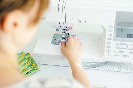 Photo pour Female hands stitching white fabric on professional manufacturing machine at workplace. Seamstress hands holding textile for dress production - image libre de droit