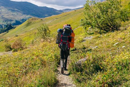 Photo pour tourist hiking in the mountains with large backpacks. Russia. - image libre de droit