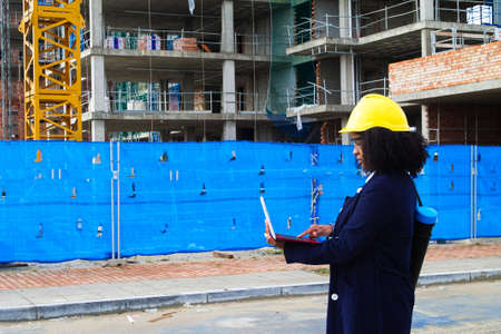 Photo pour african-american black woman construction manager in yellow hardhat set out to check the construction of the flats. The woman is holding a laptop computer in her hands - image libre de droit