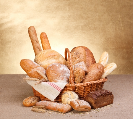 Various breads in basket on canvas tablecloth