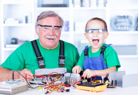 Happy grandfather and grandchild working together in workshop
