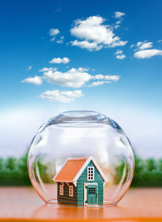 Photo for Insured house protected in glass sphere, under the cloudy bright sky - Royalty Free Image