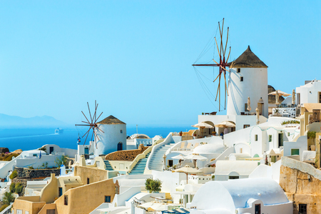 Windmills and buildings on the hill in the famous Oia town, Santorini island, Greece