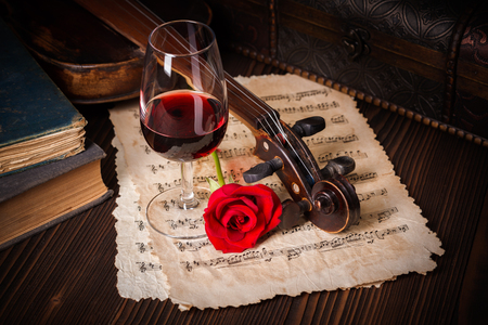 Romantic image detail with violin scroll, wine glass, books and red rose