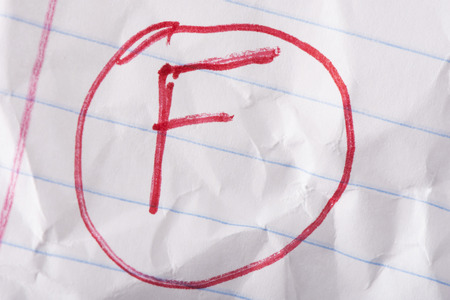 F grade written in red pen on wrinkled notebook paper.