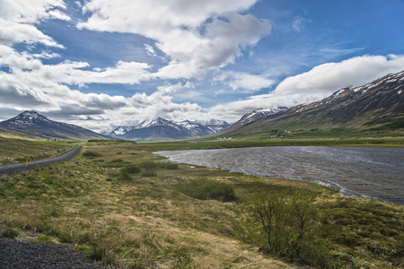 A Landscape on Trollaskagi Peninsula, Iceland with a lake, road and mountains in the background
