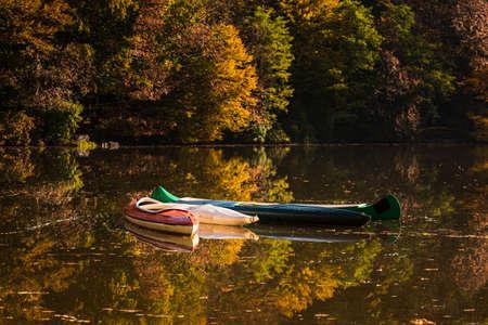 Photo pour Canoe boats on a foggy lake with Autumn foliage and tree reflections. in Styria, Thal, Austria. Autumn season theme. - image libre de droit