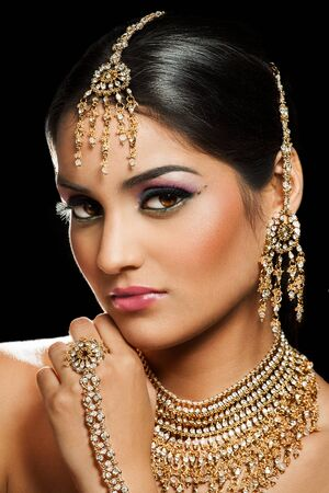 Photo for Young Indian woman wearing traditional jewelry and colorful makeup on black background. - Royalty Free Image