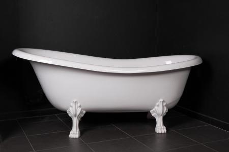 White bath on a black background in a black bathroom
