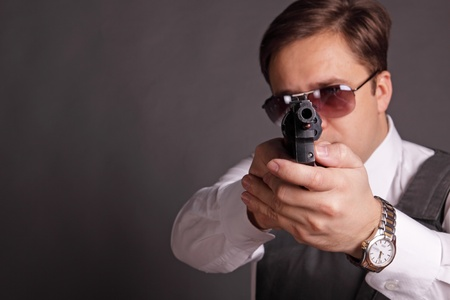 The man in a bullet-proof vest and sun glasses aims from a revolver