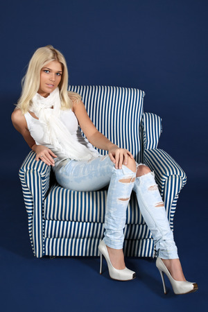 The girl in blue jeans and a white vest sits in an armchair on a dark blue background
