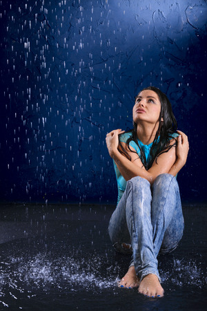 The blotted girl sits in the rain and looks upwards