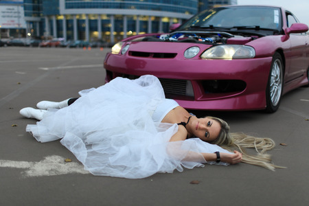 A girl in a white wedding dress lying on the pavement in front of a car