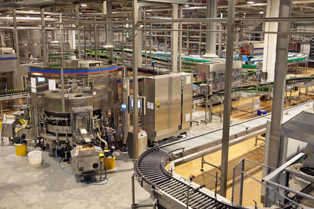The interior of the brewery. The bottling of beer. Machine bottle labelling