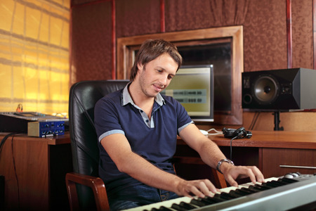 A musician is playing the melody on the keyboards in the Studio