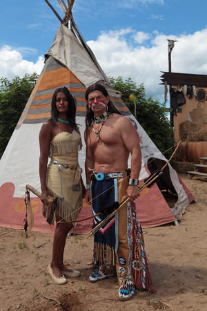 Indians man and woman stand against the background of teepee