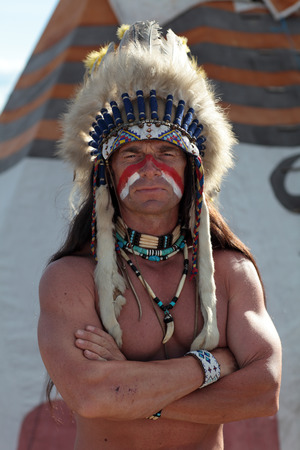 Portrait of an Indian on the background of the teepee