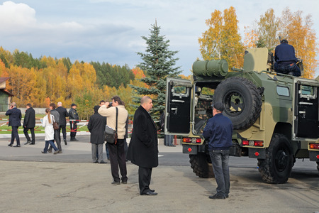 NIZHNY TAGIL, RUSSIA - SEP 26, 2013: The international exhibition of armament, military equipment and ammunition RUSSIA ARMS EXPO (RAE-2013). Visitors examine a Russian 4x4, multipurpose, all-terrain infantry mobility vehicle GAZ Tigr