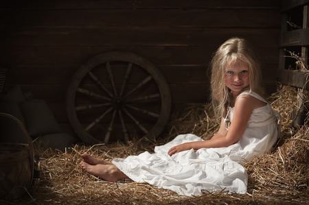 Little girl sitting alone on the hay in the barn