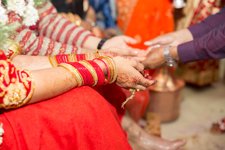 Foto de Hindu Nepali Bride and groom's Hands on the wedding day. - Imagen libre de derechos