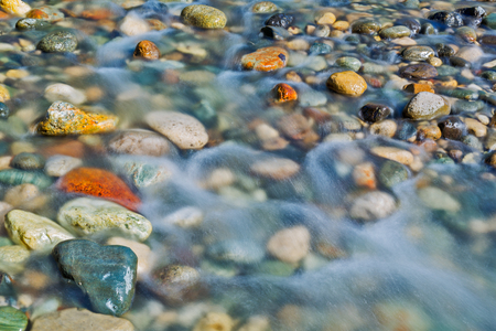 Pebble stones in the river water close up view, natural background