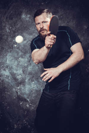Matured bearded man plays table tennis studio portrait.