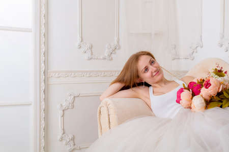 Photo for Beautiful young woman with flowers dressed in a white full wide-skirted dress sitting on the sofa - Royalty Free Image