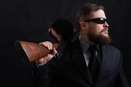Photo for Mature bearded man in sunglasses dressed in suit with tommy gun - Royalty Free Image