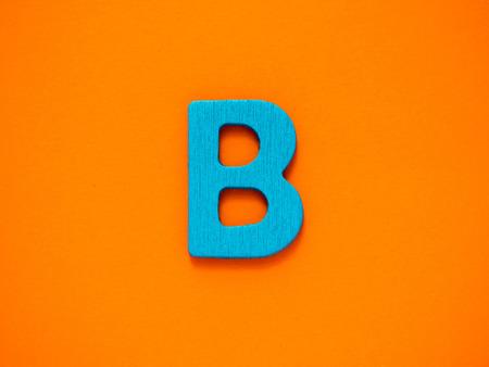 Capital letter B. Blue letter B from wood on orange background.