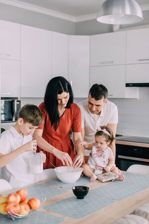 Photo pour Young family preparing food in kitchen at home - image libre de droit