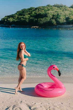 Photo pour A young woman in a swimsuit stands near an inflatable pink flamingo on the beach. - image libre de droit