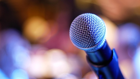 Photo pour Microphone on a blue-violet and yellow-orange background with a blurred bokeh - image libre de droit
