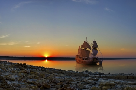 The ancient ship in the orange light of the setting sun.