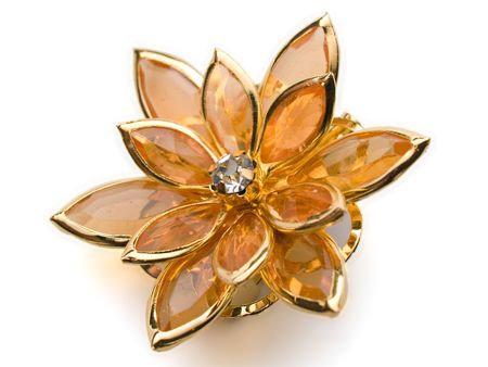 isolated flower broach ambercoloured on white background
