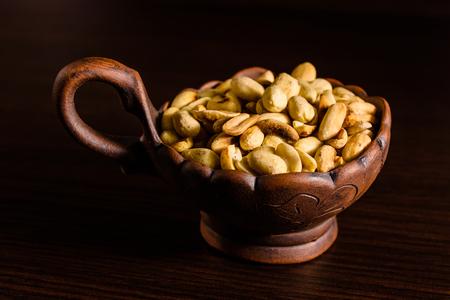 Peeled roasted peanuts in ceramic bowl on dark wooden table