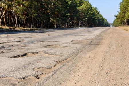 Photo for Big potholes on a damaged asphalt road - Royalty Free Image