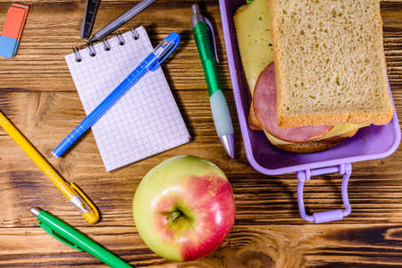 Photo for Ripe apple, different stationeries and lunch box with sandwiches on wooden table. Top view - Royalty Free Image