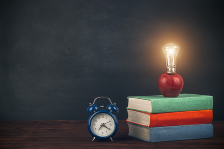 Photo pour Stack of multicolored textbooks on a wooden table, apple with light bulb and alarm clock. Back to school. - image libre de droit