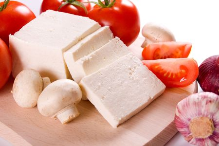 White cheese with tomato, mushrooms and garlic on wooden board