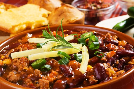Mexican chili con carne garnished with spring onion and hot peppers