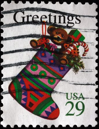A greeting Christmas stamp printed in the USA shows stocking with gifts