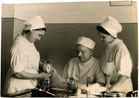 USSR - CIRCA 1960s  Reproduction of photo was take in USSR shows a doctor and two nurses with medical device, about 1960s