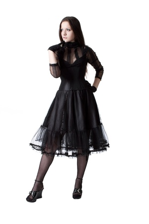 Pretty gothic girl in black dress posing over white