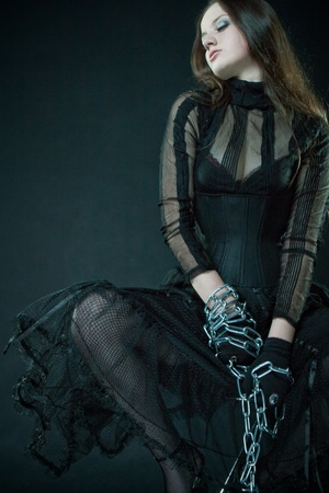 Pretty prisoner in corset bounded by chains over dark